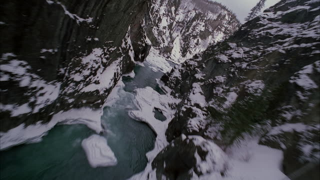 AERIAL ABOVE FROZEN RIVER IN MOUNTAIN GORGE ON CLOUDY OR OVERCAST DAY. COULD BE VALLEY OR RAVINE. SEE SNOW ON TALL ROCKY TERRAIN COVERED WITH CONIFEROUS OR EVERGREEN TREES.