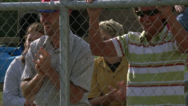 MEDIUM ANGLE OF CROWDS BEHIND A FENCE CHEERING ON LITTLE LEAGUE BASEBALL GAME. PANS OF PARENTS, MEN, WOMEN, BOYS AND GIRLS, CHILDREN, BATTING COACH, MAN WITH VIDEO CAMERA, PEOPLE IN BLEACHERS. SPECTATORS, SPORTS. KIDS.