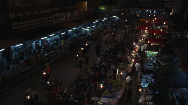 stockvideo's en b-roll-footage met high angle down of urban area marketplace, men and women walking around tables of goods, long row of motorcycles. motorcyclists driving with headlights illuminated. - men