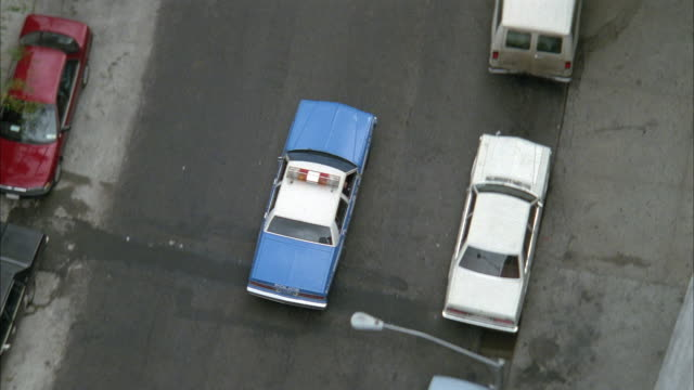 AERIAL TRACKING OF SKY BLUE AND WHITE POLICE CAR DRIVING DOWN TWO LANE CITY STREET IN URBAN AREA. SEE CARS PARKED ALONG BOTH SIDES OF STREET AND PEDESTRIANS WALKING ON SIDEWALK.