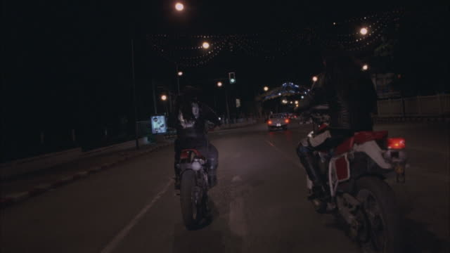 process plate of two gang men on motorcycles driving through asian city. urban area with streets, buildings, street lamps, bridges, cars, pickup trucks, tuk tuks, man and woman on motorcycles. - biker gang stock videos & royalty-free footage