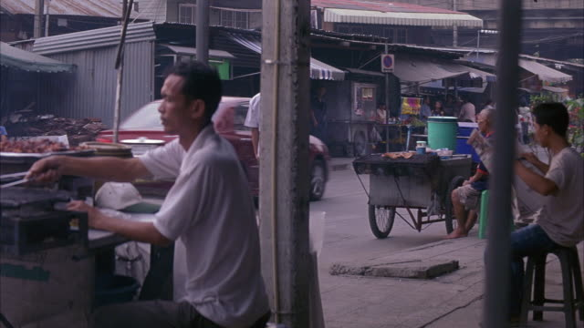 medium angle of busy, rundown city street lined with small shops and vendors. see vendor prepare goods at portable cart to frame left. see man talk and read newspaper to frame right. - bangkok stock-videos und b-roll-filmmaterial