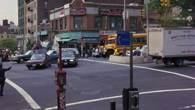 MEDIUM ANGLE OF NEW YORK CITY STREET INTERSECTION. SEE TRAFFIC ON INTERSECTION. SEE POLICE TRAFFIC CONTROLLER ON LEFT. SEE PEDESTRIANS CROSSING STREET WALKWAYS.