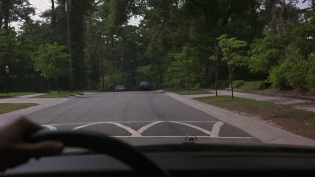 MEDIUM ANGLE FROM DRIVER'S POV FROM INTERIOR OF CAR. LOOKS LIKE CADILLAC. SEE CAR DRIVING DOWN RESIDENTIAL STREET OR COUNTRY ROAD. LOOKS LIKE UPPER MIDDLE CLASS NEIGHBORHOOD OR RESIDENTIAL AREA.