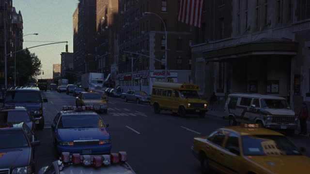 vidéos et rushes de medium angle looking down on city street traffic. see rv, yellow taxis, and yellow school bus. see nypd blue police cars parked to side of one-way street. one police car has blinking yellow hazard lights. - 1990 1999