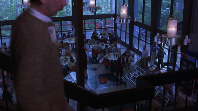 high angle down of cafe or restaurant. plastic tables and chairs occupied by customers. see blue red and white tiled floor. waiters and waitresses walk around tables. - patio stock-videos und b-roll-filmmaterial
