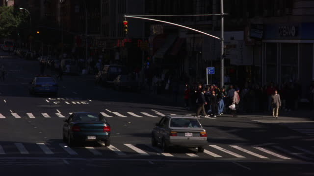 medium angle of new york city street corner. see police officer direct traffic including police car. see cars driving on street and pedestrians on sidewalk. - anno 1999 video stock e b–roll