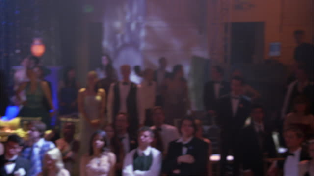vídeos de stock, filmes e b-roll de pan left to right of crowd of high school students wearing evening gowns and tuxedos. pan back and forth of couples gathered at tables in hotel ballroom. school prom, dance, party or celebration. - 1980 1989