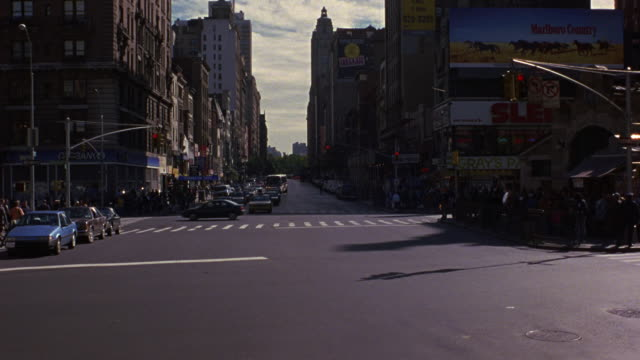 medium angle of new york city street intersection. see traffic light turn green and cars begin to move towards camera. see white 1987 buick lesabre turn left to cut off oncoming traffic and exit speeding to bottom. - anno 1999 video stock e b–roll