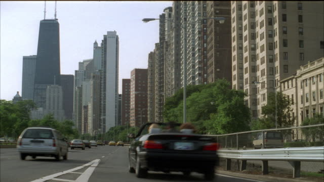 medium shot of downtown chicago skyscrapers seen from lakeshore drive. see john hancock building. see multi-story or high rise apartment buildings on right. see traffic, hazy blue sky and green trees. - blue convertible stock videos & royalty-free footage