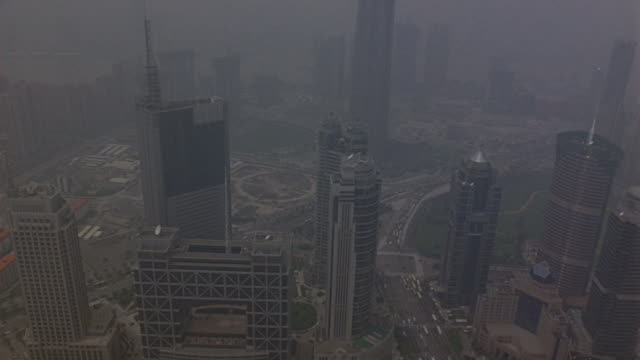 vidéos et rushes de aerial of downtown pudong area of shanghai skyline. see jin mao tower and oriental pearl tv tower in background. skyscrapers or multi-story high rises. could be office buildings or hotels. - office block exterior