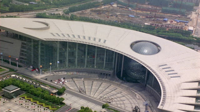 vídeos de stock e filmes b-roll de aerial of shanghai science and technology museum in downtown pudong. camera zooms out before circling museum. striking architecture with slats on roof and protruding glass sphere in center. - claraboia