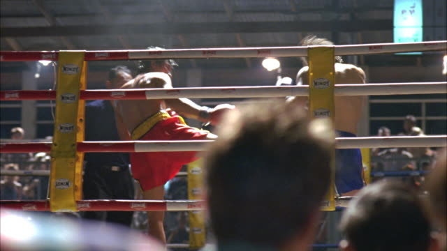 medium angle of men in boxing ring from audience pov. boxers with boxing gloves and referee stand in ring. fight begins as boxers attack, punching and kicking each other. - martial arts stock videos & royalty-free footage