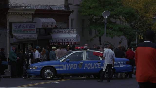 MEDIUM ANGLE OF NEW YORK CITY STREET INTERSECTION. SEE BLUE NYPD POLICE CAR. SEE CROWD GATHERED BETWEEN CAR AND STOREFRONTS, FACING AWAY FROM CAMERA.