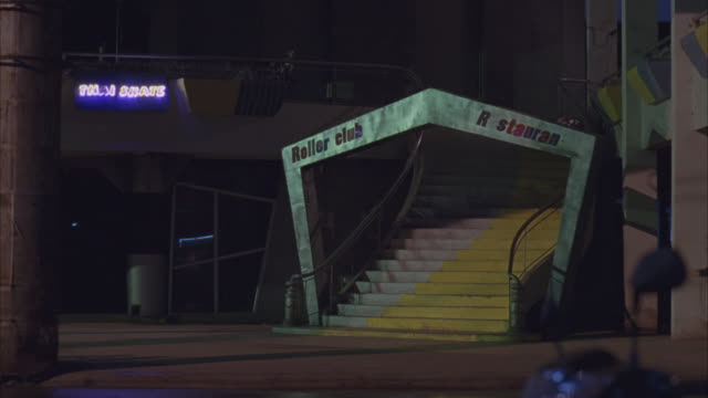 MEDIUM ANGLE OF STAIRCASE AND ENTRANCE TO POSSIBLY ABANDONED ROLLER SKATING RINK. SEE YELLOW AND WHITE STAIRCASE WITH ARCH READING ROLLER CLUB R STAURAN AT BASE.