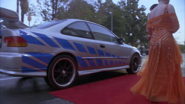 wide angle of young woman in evening gown getting out of honda civic coupe car at red carpet event. adults, men and women in crowd near spotlights. teenagers. couples. valet. - ford mustang stock videos and b-roll footage