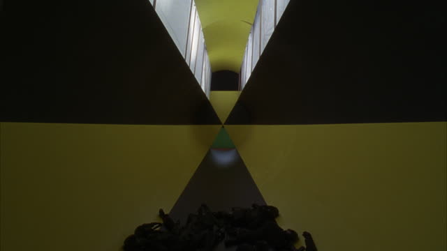 WIDE ANGLE OF LONG YELLOW AND BLACK FUTURISTIC HALLWAY OR TUNNEL. PATTERN ON WALL COULD BE RADIATION HAZARD WARNING SIGN. SEE WINDOWS ABOVE. SEE GROUP OF ARMED MEN IN UNIFORMS WITH GAS MASKS COLLAPSED ON FLOOR.