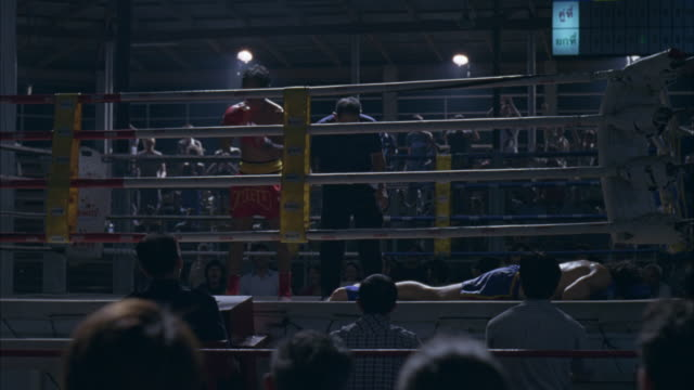 medium angle of men in boxing ring from audience pov. audience members in foreground pumping fists in air. boxer wearing red shorts and boxing gloves stands in ring. - kickboxing stock videos and b-roll footage