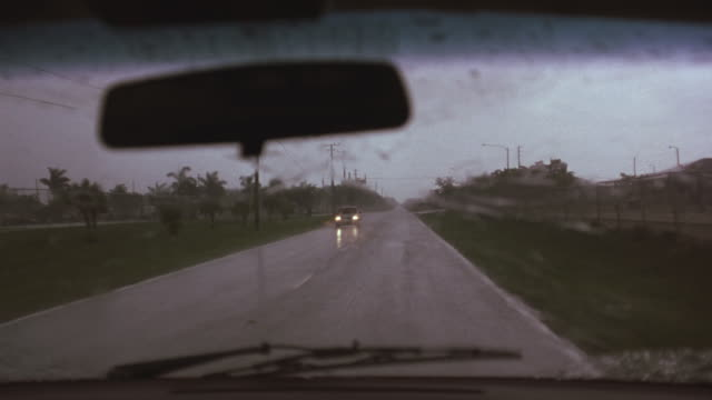 driving pov on two lane suburban road during rain storm. see windshield wipers and rear view mirror. car with headlights on approaches in opposite lane. pov from passenger side pans to the right. - headlight stock videos & royalty-free footage