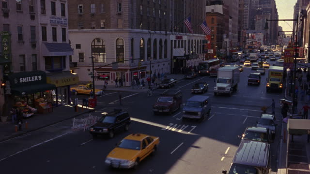 wide angle down of city street traffic on one-way street. see multi-story buildings framing either side of street. see american flags hanging off building in background. - 1999 stock videos & royalty-free footage