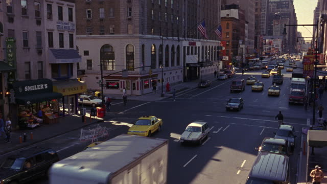 wide angle down of city street traffic on one-way street. see multi-story buildings framing either side of street. see american flags hanging off building in background. - one way stock videos and b-roll footage