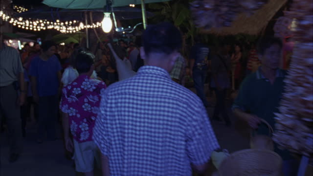 STEADICAM THROUGH BUSY MARKETPLACE. POV PASSES TAXIS AND TUK TUKS AT MARKET ENTRANCE. SEE CROWD SHOPPING AT STREET VENDORS.
