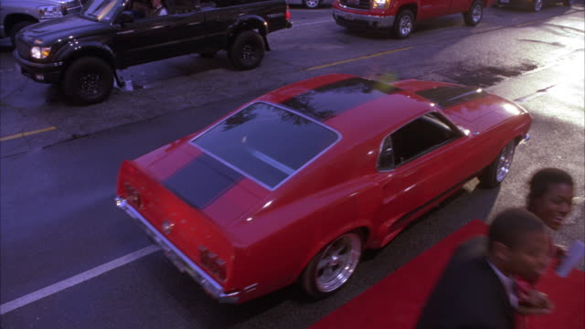 vídeos de stock, filmes e b-roll de wide angle of 1969 mustang car and stretch hummer limo arriving at red carpet event. teenagers, high school students or couples wearing evening gowns and tuxedos emerge and walk past valets, crowd of men and women, possibly parents, and doormen. - limousine
