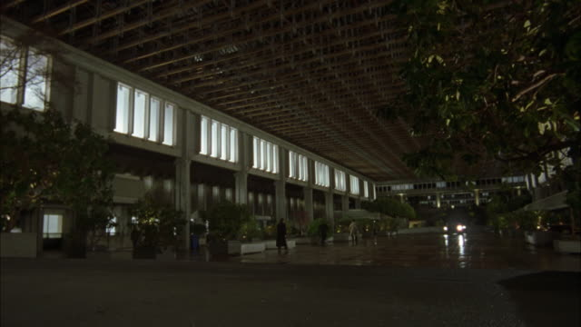WIDE ANGLE OF PLAZA OR SQUARE SURROUNDED BY CONCRETE BUILDINGS. SEE AWNING EXTENDING FROM BUILDING FRAME LEFT WITH LIGHTS SHINING FROM WINDOWS.