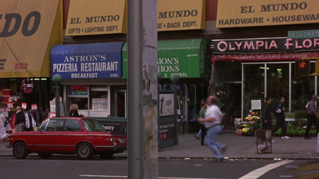 medium angle of new york city street. see shops signs reading astron's pizzeria restaurant el mundo gifts and lighting dept and olympia florist. see pedestrians on sidewalk. see traffic drive right to left. - anno 1999 video stock e b–roll