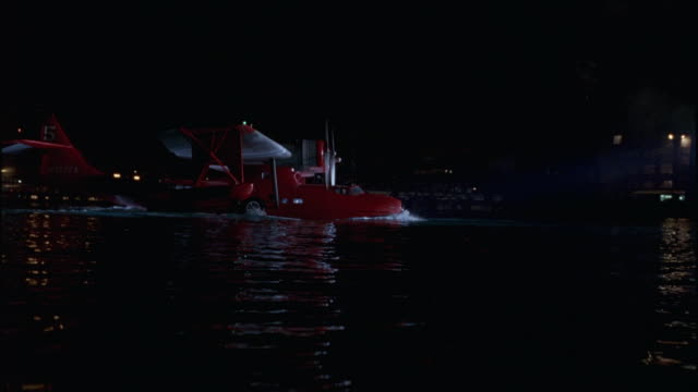 wide angle of seaplane in water at harbor or sea port. could be airplane take-off, landing, or taxiing. camera is from water level pov, moves up and down with waves, pans to follow plane left to right. - propeller video stock e b–roll