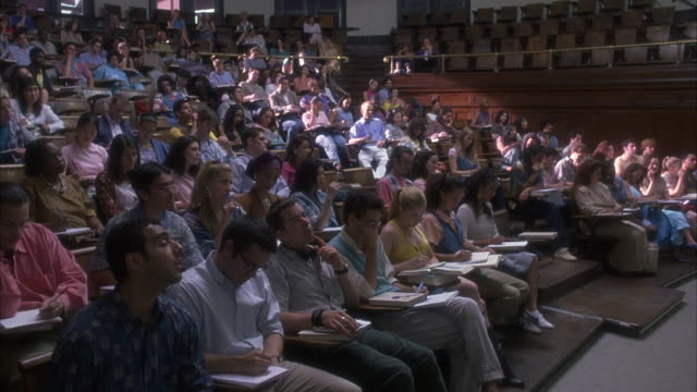 est wide angle on students sitting inside a lecture hall taking notes. - ivy league university stock videos and b-roll footage