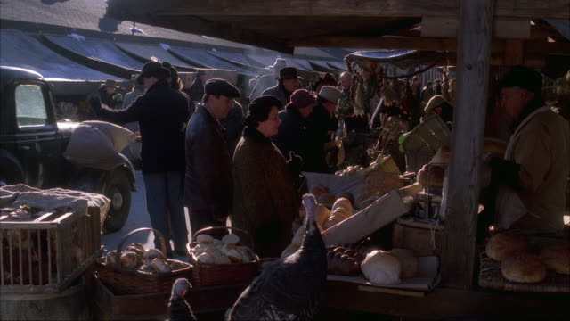 MEDIUM ANGLE OF MARKETPLACE STAND WITH BREAD AND CAGES OF BIRDS AND TURKEYS ON SIDE. CUSTOMERS STOP BY AND PURCHASE BREAD. MARKETPLACE IS CROWDED WITH PEOPLE IN LONG COATS, JACKETS AND HATS. COULD BE USED FOR THANKSGIVING SHOPPING.