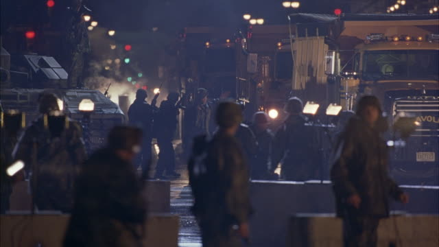 WIDE ANGLE OF MILITARY CAMP SET UP IN MIDDLE OF NEW YORK CITY STREET. SEE SOLDIERS RUNNING AROUND. ROADBLOCKS SET UP. SEE DUMP TRUCKS DRIVING AROUND CAMP.