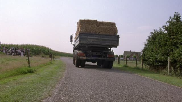process plate of back of large black dump truck with bales of hay in bed driving down country road. see corn on left and field on right bordered by fence. - dump truck stock videos and b-roll footage
