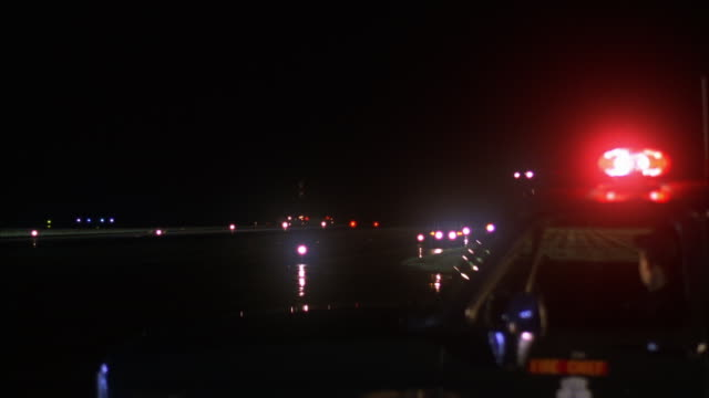 MEDIUM ANGLE OF LIT RUNWAY AT NIGHT. SIREN OF FIRE SUV FLASHES IN FOREGROUND, MAN IN DRIVER'S SIDE. SEE AIR FORCE ONE AIRPLANE APPEAR FROM DISTANCE, AIRPLANE DESCENDS AND LANDS.