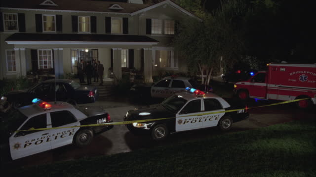 vidéos et rushes de wide angle of two story upper class colonial style house with police detectives on front porch. bridgeport police cars with flashing lights or bizbars, detective's car and ambulance parked in driveway. police tape indicates crime scene. - détective