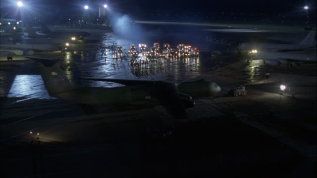 vídeos de stock e filmes b-roll de pull back from air traffic control tower with spotlight shining on runway full of fire engines and rescue vehicles with lights and sirens on. sides of runway lined with parked jets. - carro de bombeiro