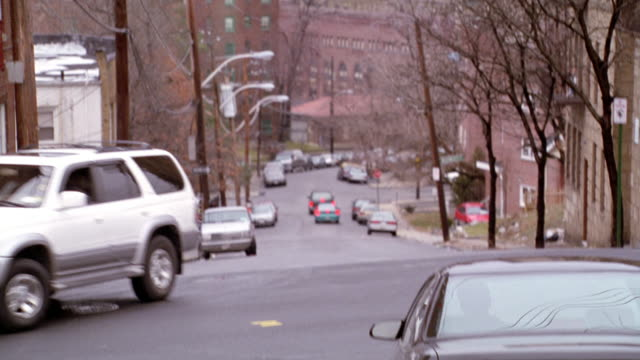MEDIUM ANGLE OF TRAFFIC SIGNAL WITH RED SIGNAL LIT. SEE APARTMENT BUILDINGS ON RIGHT AND LEFT SIDES. SEE PHONE AND ELECTRICAL LINES ACROSS SCREEN. SEE SMOKE STACK IN BACKGROUND. SEE TREE COVERED HILL IN FAR BACKGROUND.