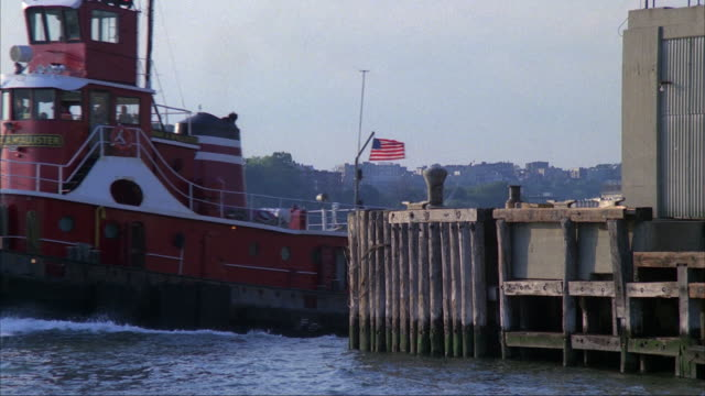 vidéos et rushes de medium angle of hudson river facing new jersey in background. boat dock and building in foreground. red tugboat with american flag pulls barge with junk or garbage, appears from right and moves across to left. - remorqueur