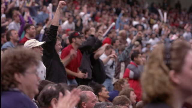wide angle of crowd cheering in stadium seats. see people standing up, clapping, waving noise makers, and yelling. could be reaction to play or scoring. could be football, baseball, basketball, or hockey game at sports arena. spectators. - spettatore video stock e b–roll