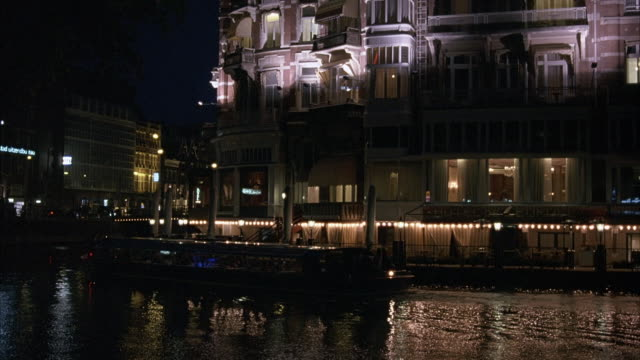 WIDE ANGLE OF WATERFRONT VICTORIAN STYLE BUILDING. COMMERCIAL AREA AT NIGHT. SEE FERRY TRAVELING FROM RIGHT TO LEFT IN WATER IN FOREGROUND, TURNS CORNER AND OUT OF POV.