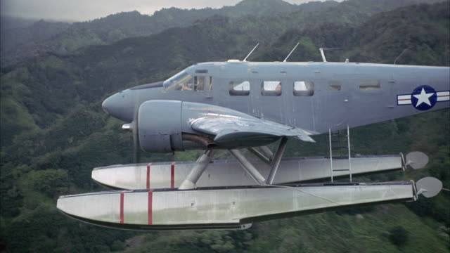 AERIAL OF ARMY OR MILITARY SEAPLANE FLYING OVER HILLS COVERED WITH GREEN TREES AND VEGETATION. COULD BE TROPICAL AREA. ZOOM OUT, SEE ROPE ATTACHED TO PONTOON WAVING IN AIR. SEE MIST OR CLOUDS IN DISTANCE OVER HILLTOPS.