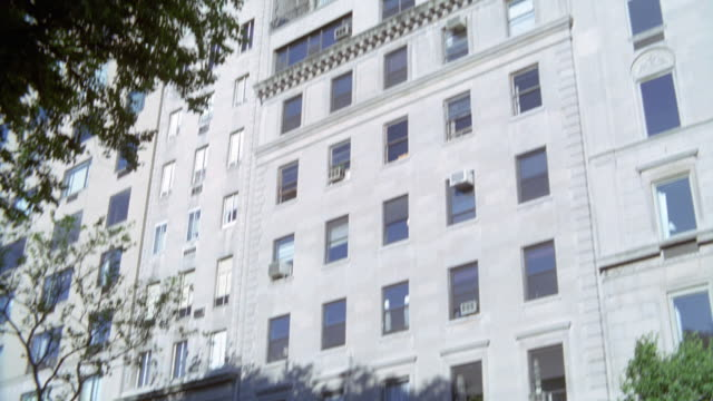 PAN DOWN OF FIFTEEN STORY LIGHT COLORED STONE APARTMENT BUILDING OR HOTEL. SEE TREE IN LEFT FOREGROUND. PANS DOWN TO SHOW ENTRANCE OF BUILDING WITH AWNING EXTENDING OVER SIDEWALK.