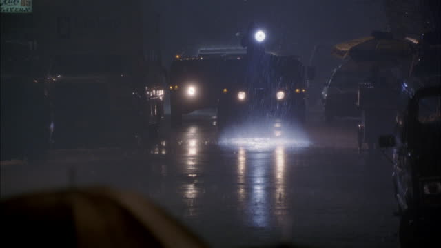 medium angle of new york city street. see military convoy driving toward camera. led by hummer with spotlight on roof. see reporters and soldiers walking across camera carrying umbrellas in heavy rain. - hummer stock videos and b-roll footage