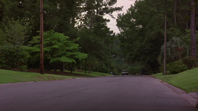 medium angle of two lane street in upper class residential neighborhood. see lush green trees flanking road. see tan buick electra estate wagon drive towards pov at left side of road. - cadillac stock videos & royalty-free footage