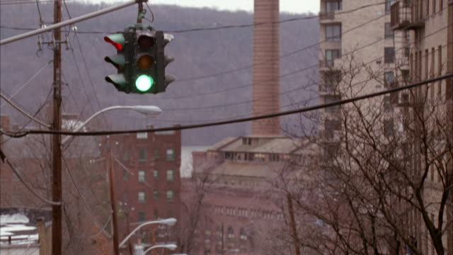 MEDIUM ANGLE OF URBAN AREA WITH TALL BRICK APARTMENT BUILDINGS ON RIGHT, A TALL SMOKE STACK IN CENTER AND A TREE COVERED HILL IN BACKGROUND. SEE POWER LINES CROSSING SCREEN AND A TRAFFIC SIGNAL IN RIGHT FOREGROUND WITH RED LIGHT LIT.