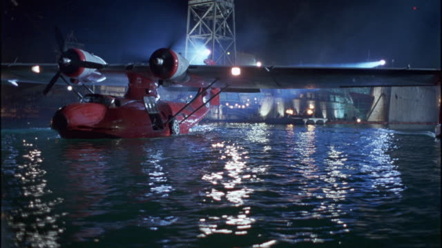 wide angle of red seaplane or water plane taxiing in industrial harbor or large sea port. camera circles plane revealing multiple towers, cranes, buildings, large ships and tankers, fires burning on docks. propeller airplanes, ocean. - propeller video stock e b–roll