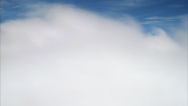 AERIAL OVER AND THROUGH WHITE FLUFFY CUMULUS CLOUDS IN BLUE SKY. SEE OCCASIONAL WISPY CIRRUS CLOUDS. POV TURNS MULTIPLE TIMES. SEE POV DIP UNDER CLOUDS TO SEE COUNTRYSIDE TERRAIN.