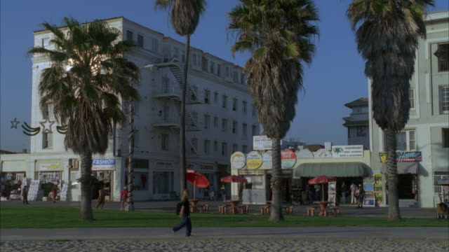 medium angle shot of apartment buildings or condominiums and  shops at venice beach boardwalk. see palm trees and pedestrians. see red umbrellas and tables. - venice california stock videos & royalty-free footage