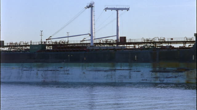 MEDIUM ANGLE OF LARGE INDUSTRIAL TANKER SHIP. SEE MULTIPLE LEVELS OR DECKS OF TANKER AND SUN SETTING IN BACKGROUND. SEE TANKER BLOCK OUT SUN AND REVEAL BLUE AND WHITE COLOR OF SHIP.